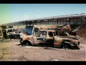 Three burnt pickup trucks with pipeline overpass in the background, Pecos River, Eddy County, New Mexico, August 19, 2000.